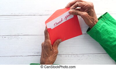 senior women's hand holding thank you letter , rear view ,