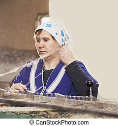 Senior worker pulling out thread while working on machine