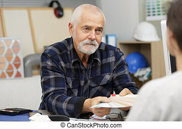 senior worker talking to customer in office
