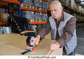 senior worker taping a box in warehouse