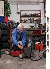 Senior worker with lawn mower in workshop