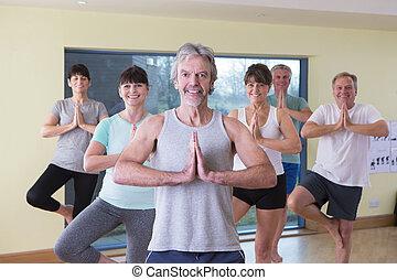 Senior yoga class posing for the camera
