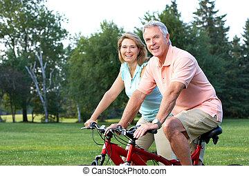 seniors couple biking - Happy elderly seniors couple biking...