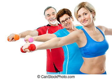 Seniors doing fitness exercises with help of trainer at ...