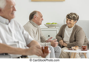 Seniors enjoying common conversation at recreation room
