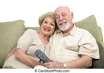 A happy senior couple watching television together. White background.