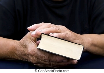 Senior's hands on old Bible