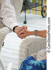 Seniors on a porch holding hands
