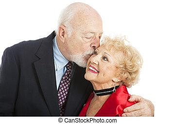 Seniors - Holiday Kiss - Adorable senior woman getting a ...