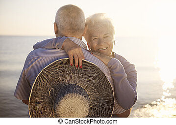 Seniors hugging by the sea