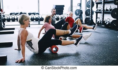 Seniors in gym with coach exercising with foam roller. -...