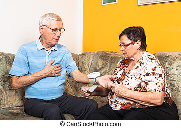 Senior couple checking blood pressure at home.