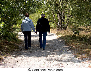 Seniors, middle aged people walking in forest.
