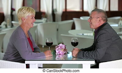 Seniors on a date - Husband and wife enjoying glass of red...