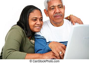 Seniors On Computer - Minority couple set against a white...