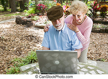 Seniors on Computer with Copyspace - Senior couple on the...