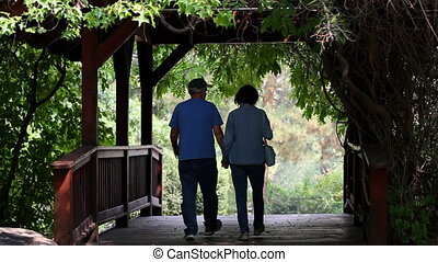 Seniors On Covered Bridge - Two senior adult retirees walk...