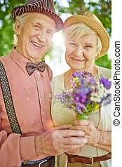Elderly man and woman spending summer day in park