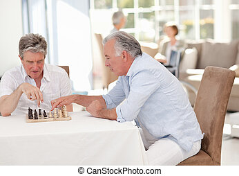 Seniors playing chess in the living room
