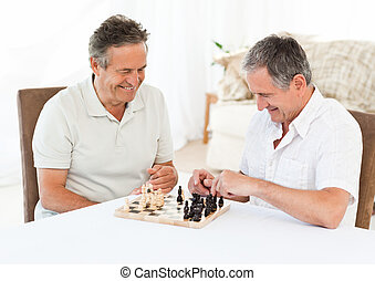 Seniors playing chess on the table