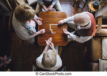 Seniors Playing Dominoes - Aerial shot of four senior adults...