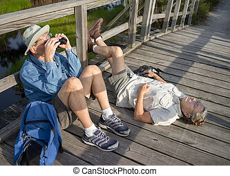 Seniors Relaxing and Birdwatching - Mature hiking couple...