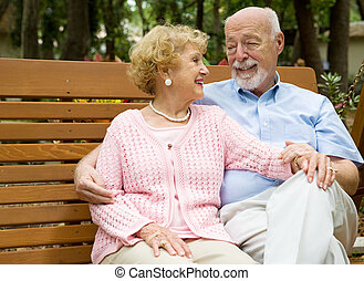 Seniors Relaxing in Park - Happy senior couple relaxes...