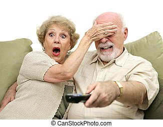 A senior couple shocked by what they see on television. She's covering his eyes and he's changing the channel. White background.