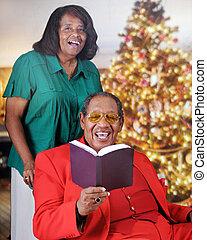 Seniors Sing at Christmas - A senior adult couple singing...