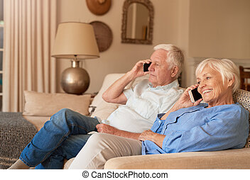 Seniors sitting on their sofa at home talking on cellphones...