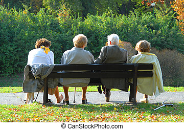 Seniors relaxing in the autumn park