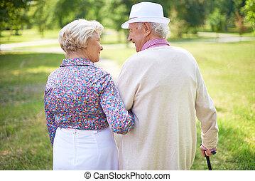 Seniors walking - Back view of happy senior couple talking...