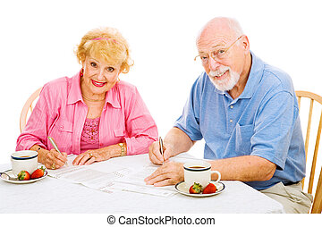 Seniors with Absentee Ballots - Senior couple filling out...