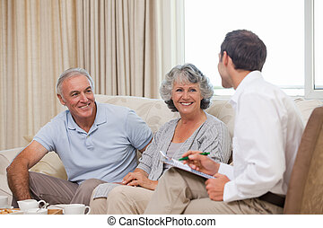 Seniors with assurance man at home