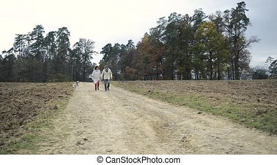 Seniors with dog on a walk in colorful autumn nature
