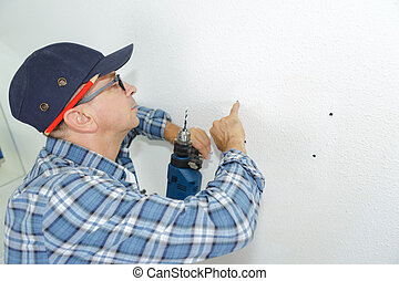 seniro man drilling a hole in a wall