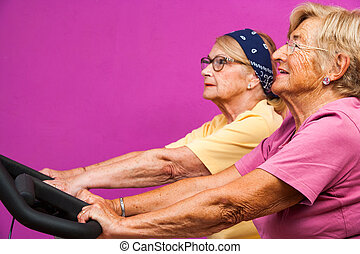 Senoir women working out on bicycles in gym