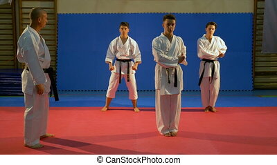 Sensei supervising karate black belt practitioners performing kata at the dojo