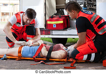 Senseless woman lying on stretcher - Horizontal view of...