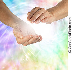 Healing hands cupped with white energy between on a swirling rainbow colored background
