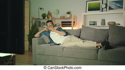 Sensitive young Arab is watching TV crying looking at television screen with sad face lying on couch in cozy apartment. Unhappy people and leisure concept.
