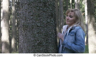 Sensitive beautiful woman caressing and embracing a tree in...
