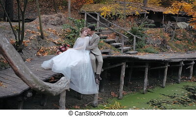 Sensitive emotional young wedding couple sitting on small wooden bridge by swampy lake with closed eyes, enjoying solitude in beautiful nature by autumn forest. Bride leaned on groom at the bridge.