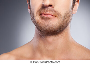 Sensitive skin? Cropped image of young man with stubble grimacing while standing isolated on grey background
