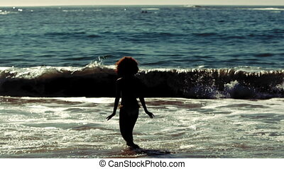 Sensitive woman going into the sea - Silhouette of sensitive...