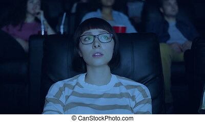 Sensitive young woman watching interesting drama in cinema...
