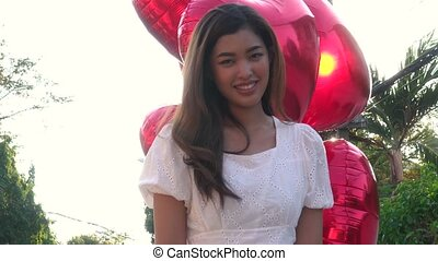 Sensual Asian woman with balloons in park - Attractive Asian...