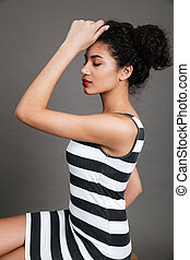 Sensual attractive african american young woman sitting and posing
