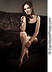 Sensual attractive young woman in a silk pajamas poses on a sofa.