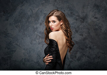 Sensual attractive young woman in classical dress with open back